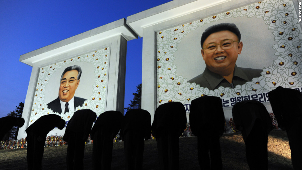 North Korean citizens bow before the portraits of the founding father Kim Il-Sung, left, and his son Kim Jong-Il, in Pyongyang, North Korea on Monday, April 9, 2012. April 15 marked the 100-year anniversary of the founder's birth and journalists were allowed inside the country.