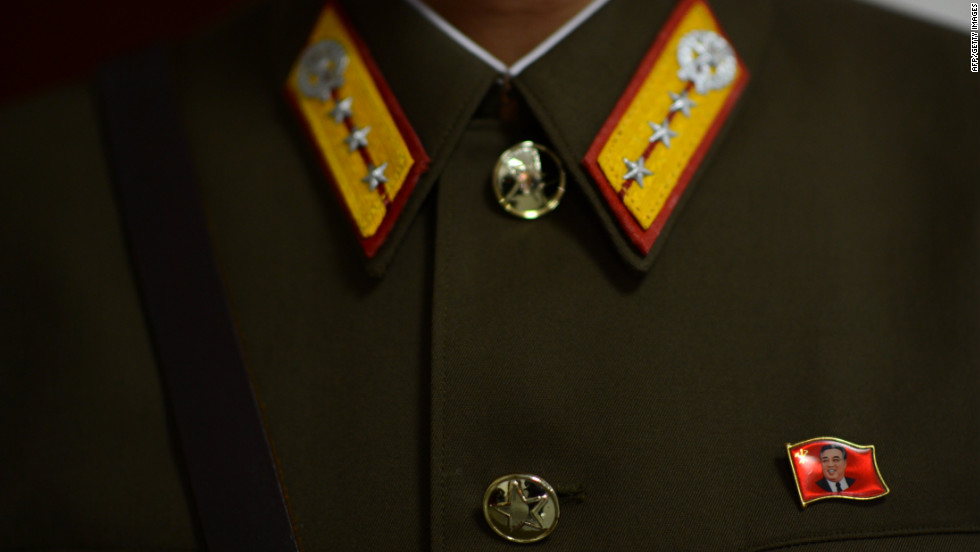 A pin with the face of Kim Il-Sung is affixed to the uniform of a North Korean soldier standing guard at the space center in Pyongyang on Wednesday, April 11.