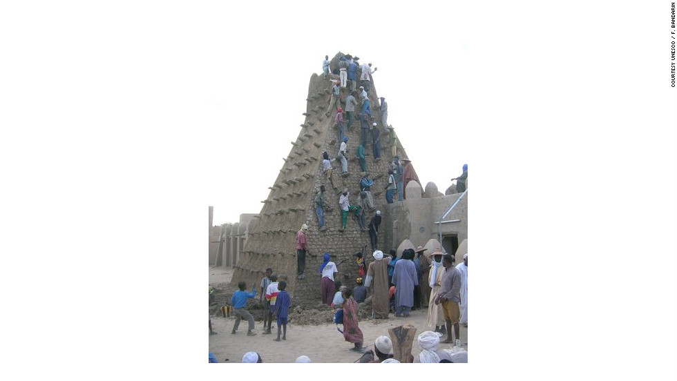 "In this archive picture, locals climb the Sankore Mosque. This week, UNESCO issued new calls for the protection of Timbuktu. ""Mali's cultural heritage is a jewel whose protection is important for the whole of humanity,"" said UNESCO director-general Irina Bokova."