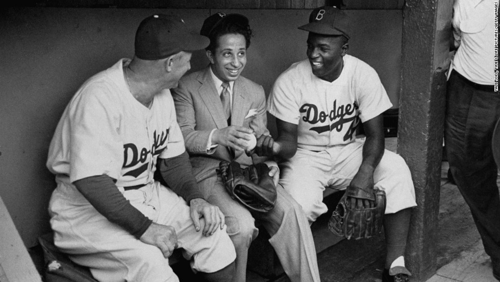 "Brooklyn manager Charlie Dressen, Iraq's 17-year-old King Faisal II (invited to the U.S. by President Truman) and Jackie Robinson chat in the Dodger dugout in 1952. The caption — in the odd, clipped language LIFE employed at the time — that accompanied this picture when it ran in LIFE: ""Baseball badinage in Dodger dugout pleased king until his uncle made him remove ball cap as undignified. 'I guess I'd better leave now,' said king."""