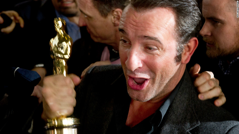 "Jean Dujardin holds his Oscar for ""The Artist,"" but will it offset for the loss of France's triple-A credit rating?"