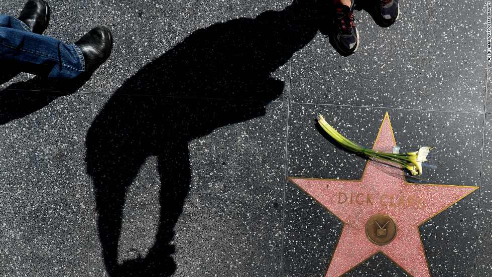 "A sillhouetted photographer take pictures of Dick Clark's Hollywood Walk of Fame Star on Wednesday. Clark, who created and hosted ""American Bandstand,"" died of a massive heart attack Tuesday at age 82."