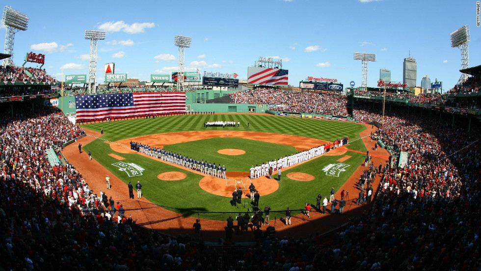 The Boston Red Sox and the Tampa Bay Rays line up for the national anthem during the home opener.
