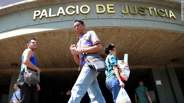 People walk in front of Venezuela's courthouse headquarters in Caracas on April 9, 2012.