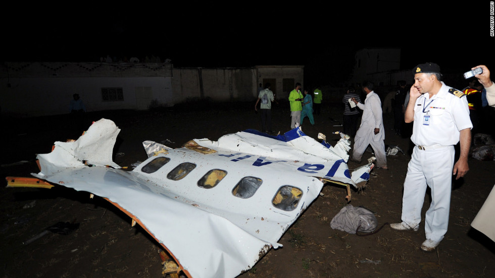 A Pakistani airline official, right, stands next to the wreckage of the Bhoja Air Boeing 737 plane. Debris and body parts were scattered across the crash site as workers sifted through the wreckage in the heavily populated residential area.