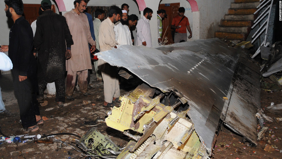 Pakistani villagers survey debris from the crash.
