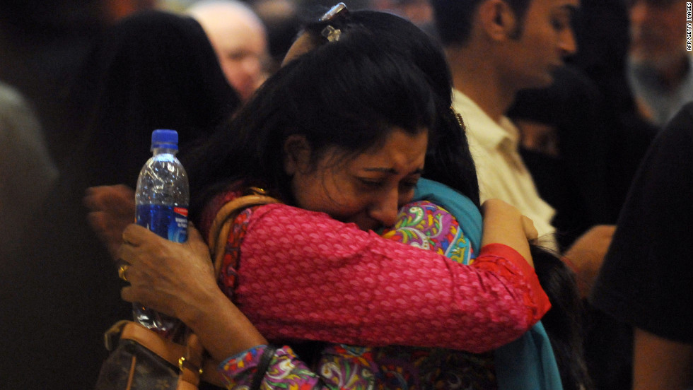 Two women comfort each other at Karachi Airport.