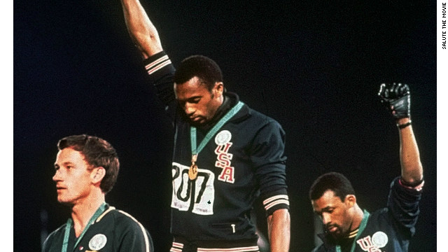 Tommie Smith, center, and John Carlos, right, raise their fists while standing on the podium at the 1968 Mexico Olympics.