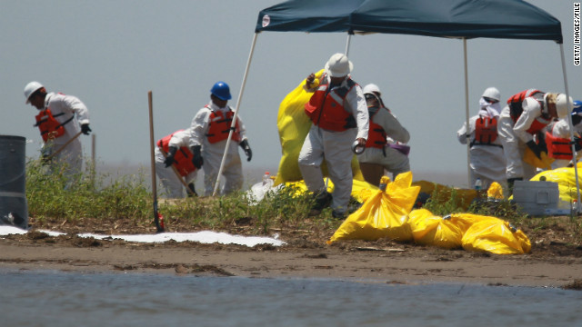 SOUTH PASS, LA - MAY 12: Workers clean a beach after tar balls washed up as efforts continue to contain BP's massive oil spill on May 12, 2010 in South Pass, Louisiana. The Deepwater Horizon oil rig operated by BP is leaking an estimated rate of 1,000-5,000 barrels of oil a day into the Gulf and the slick has now reached nearby land. Efforts to contain the spill have done little to slow its flow. (Photo by Joe Raedle/Getty Images)