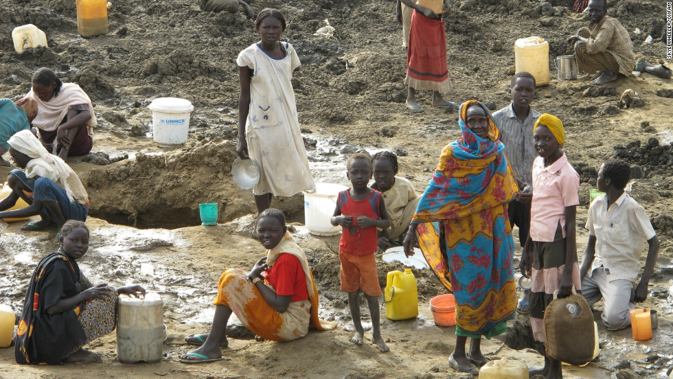 Refugees are left digging around the bottom of a dried-up cattle pond to try and supplement their meager water supplies.