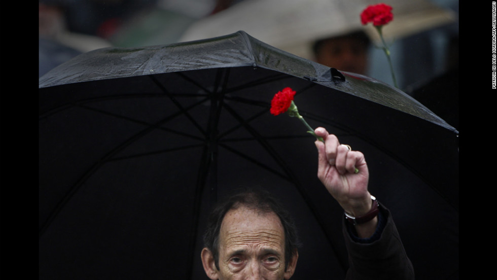 A man holds a red carnation, a symbol of the 1974 Portuguese revolution, as he marches in downtown Lisbon on Wednesday.