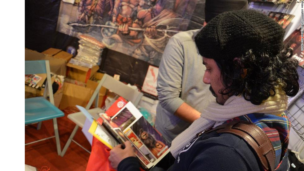 "An attendee reads through a ""Vimanika"" comic book at the 2nd Annual Comic Con India in New Delhi."
