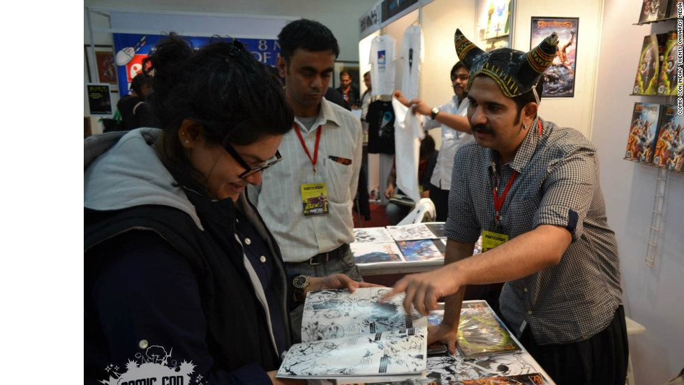 A convention exhibitor chats with an attendee at the 2nd Annual Comic Con India in New Delhi.