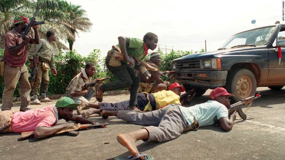 Rebels loyal to Charles Taylor take position behind a truck in May 1990 in Monrovia.