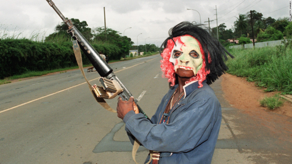 A masked rebel loyal to warlord Charles Taylor patrols in the streets of Monrovia in August 1990.