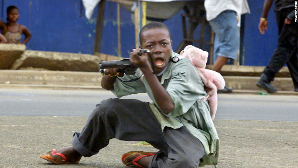 A child soldier wearing a teddy bear backpack points his gun at a photographer in a street of Monrovia in June 2003.