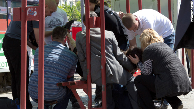 People try to help a woman injured by one of the blasts in the eastern Ukrainian city of Dnepropetrovsk on Friday.