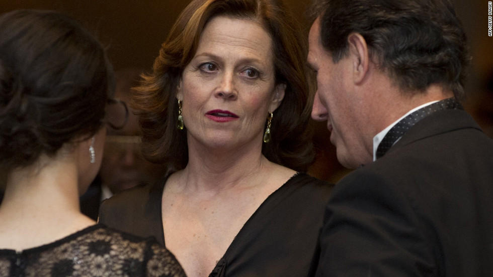 Actress Sigourney Weaver and former Republican presidential hopeful Rick Santorum, right, socialize at the dinner.