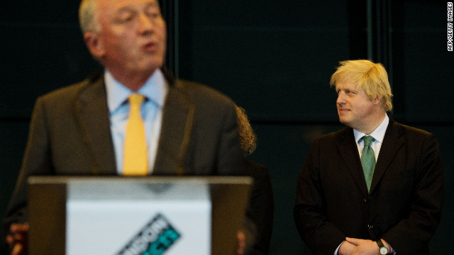 Boris Johnson (R) looks on as his main opponent Ken Livingstone speaks after the election results are announced.