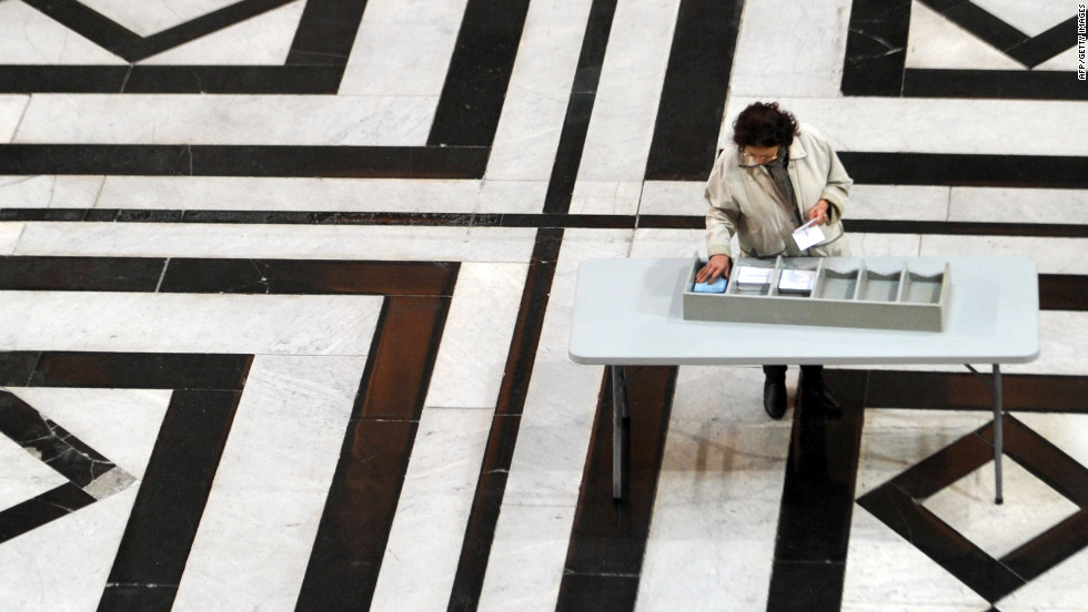 A woman picks up ballots before voting at a polling station in Marseille, France, on Sunday.