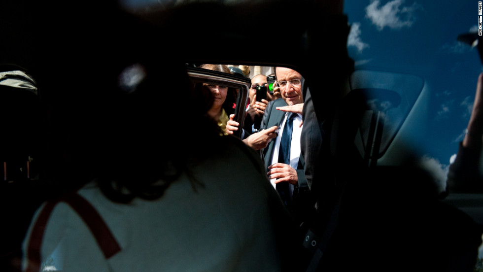 Francois Hollande squeezes past members of the public to get into a car Sunday during a visit to Vigeois, in central France.