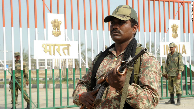 An Indian Border Security Force soldier stands guard beside the gates at the India-Pakistan Wagah Border .