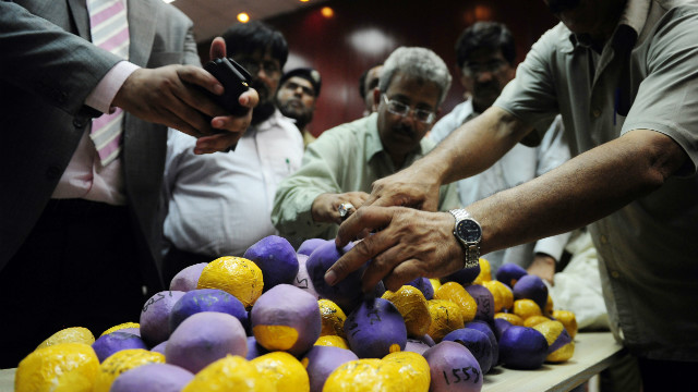 Pakistan customs officials display seized heroin concealed inside tape and balloons in Karachi.