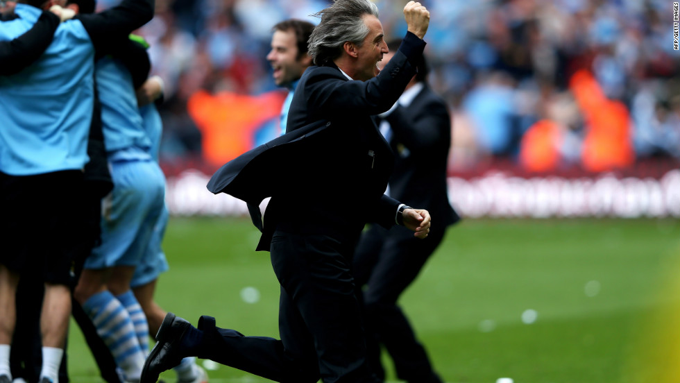 City manager Roberto Mancini (center) runs to greet his jubilant players after their breathtaking victory.