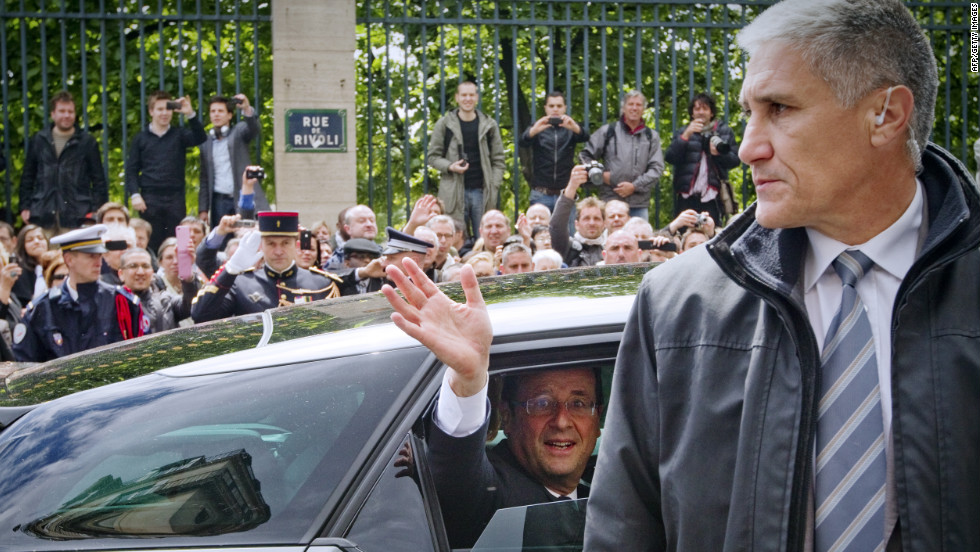 Hollande waves to the crowd from his car outside the Tuileries Garden in Paris.