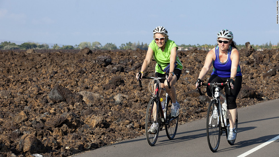 Fit Nation Challenge participants Nancy Klinger, left, and Adrienne LaGier bike through the lava fields on the Big Island of Hawaii.