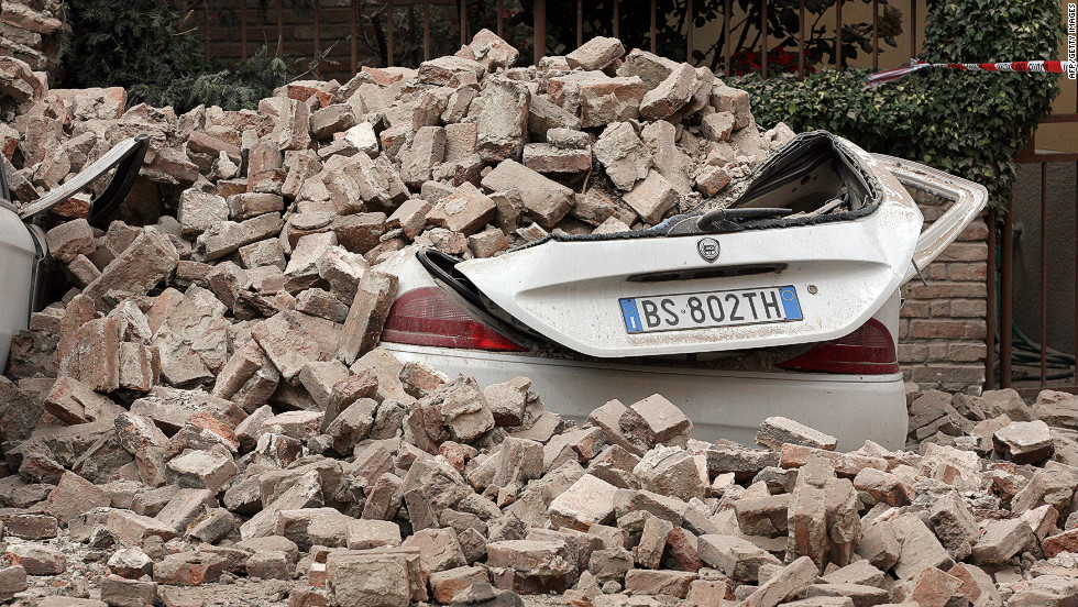 Cars are left buried under rubble from Sunday's earthquake in Finale Emilia.