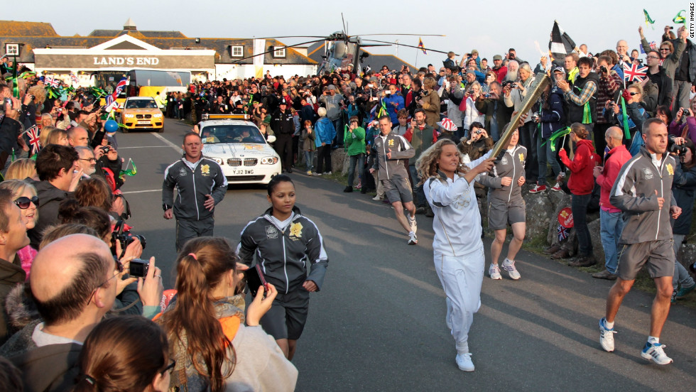 Surfer Tassy Swallow carries the flame as it leaves Land's End. She is one of 8,000 torch-bearers who will transport the flame on its 70-day journey to the Olympic Stadium in east London.