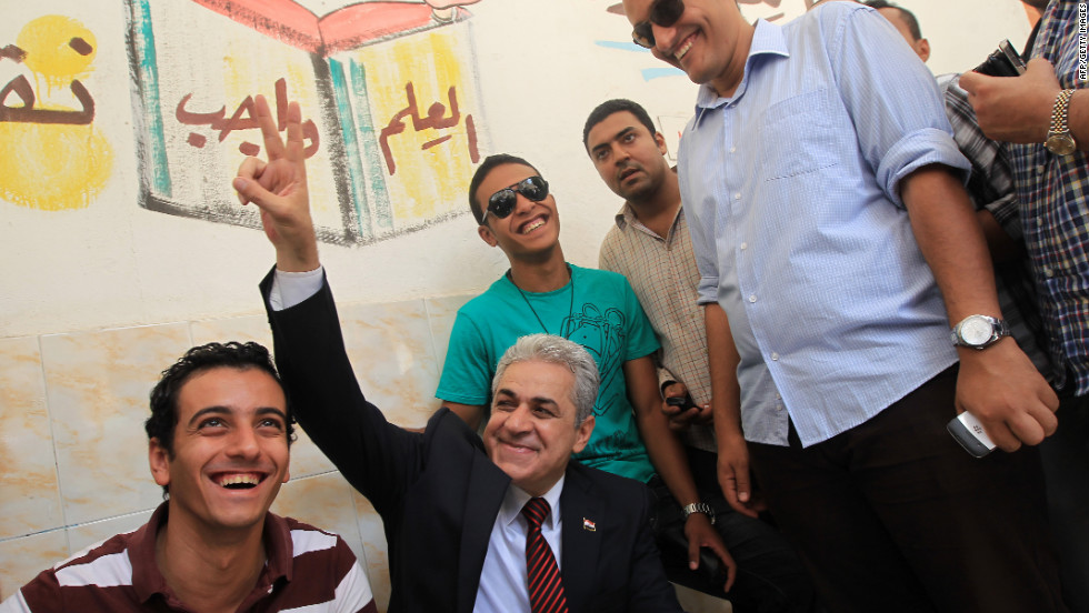 Presidential candidate Hamdeen Sabahy, a leftist dark-horse contender, flashes a sign of victory as he waits to vote at a Cairo school.