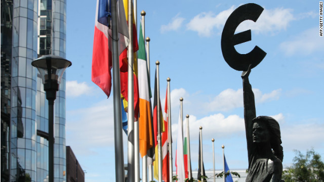 A statue holding the symbol of the Euro, the European common currency, stands in front of the European Parliament building.