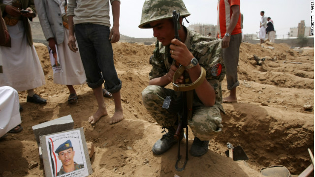A Yemeni soldier sits next to the grave of a comrade who was killed in a suicide bombing earlier in the week.
