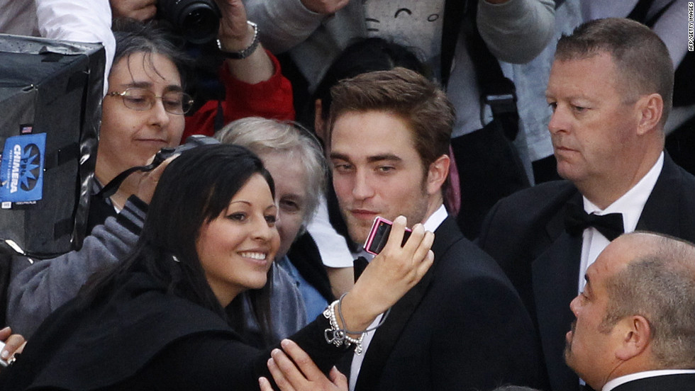 "British actor Robert Pattinson signs autographs and poses for photos with fans prior to the screening of ""Cosmopolis"" on Saturday."