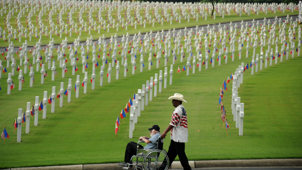 A man pushes an elderly man past the graves Sunday at the Manila American Cemetery.