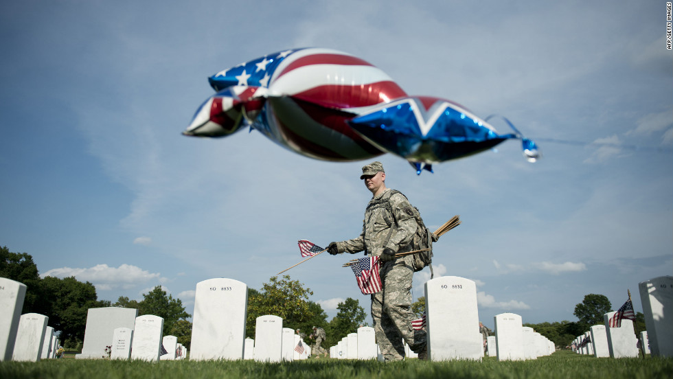 A soldier plants a flag at Arlington National Cemetery on Thursday.