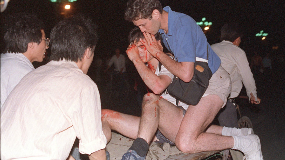 An injured foreign journalist is transported away from the Tiananmen Square clash.