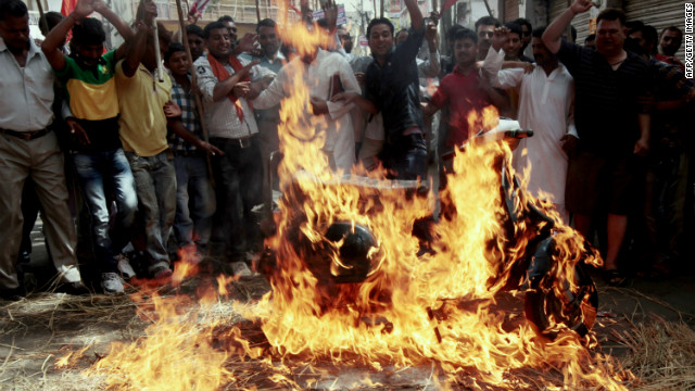 Shiv Sena activists chant slogans after setting fire to a scooter during a strike against a petrol price hike in Jammu on May 31, 2012