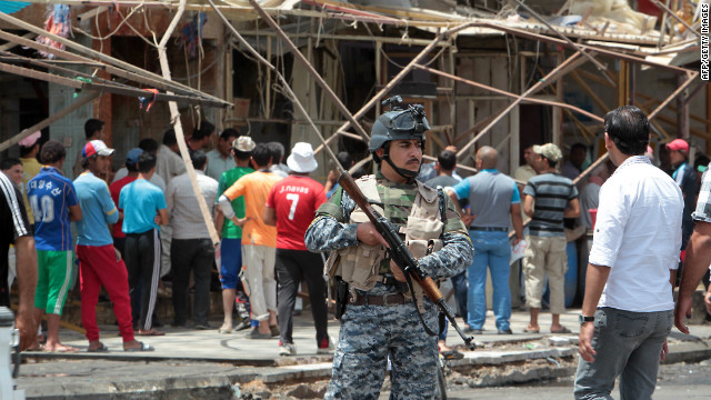 An Iraqi policeman stands guard at the site of a blast as people inspect damages in Baghdad on May 31, 2012.
