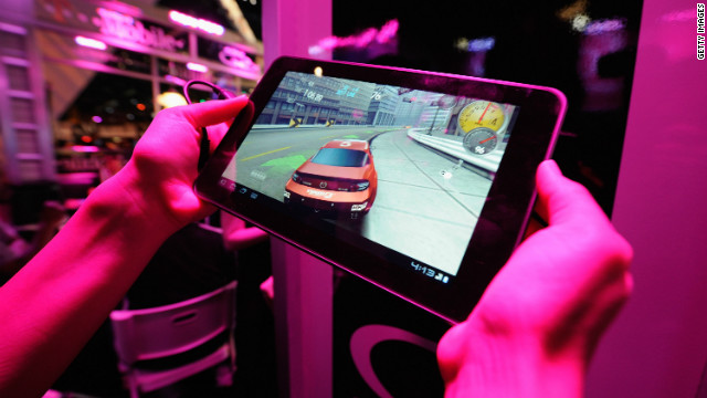 An exhibitor plays a racing game on a tablet at last year's E3. Gaming has been expanding from consoles to mobile devices.