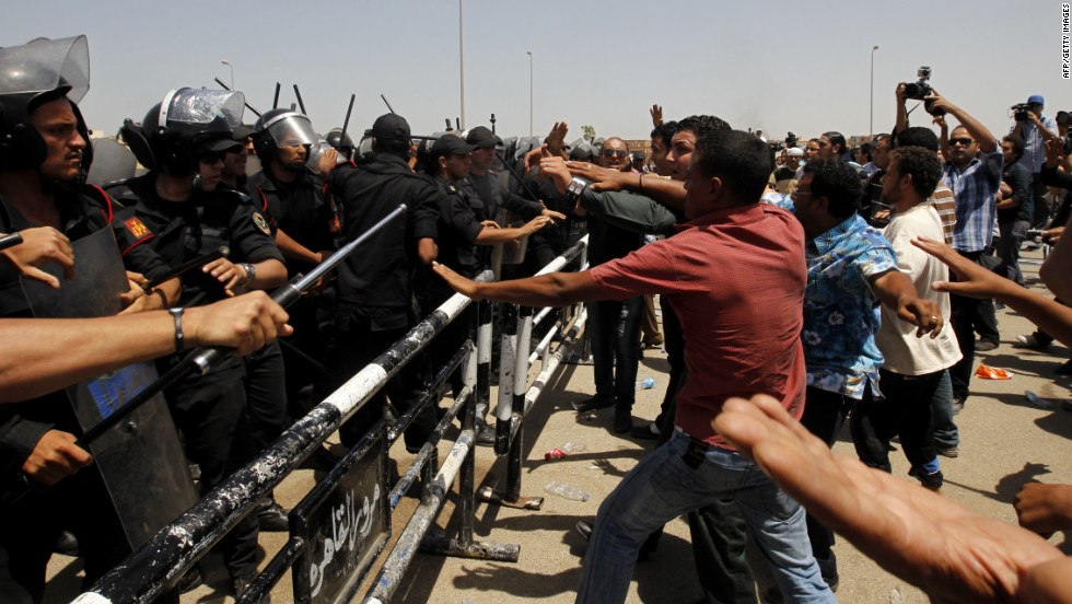 Protesters and police officers clash after the announcement of Mubarak's guilty verdict.