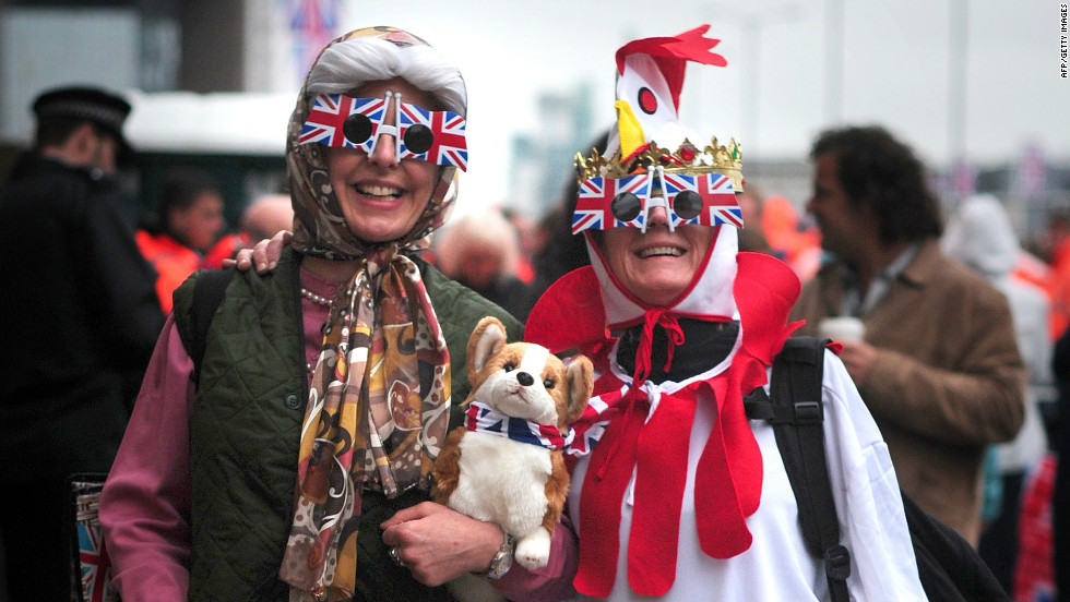 "Two pageant spectators dressed as the queen (complete with corgi) and a ""coronation chicken"" pose for a photograph along the River Thames. Thousands are expected to turn out for the pageant to celebrate the queen's Diamond Jubilee"