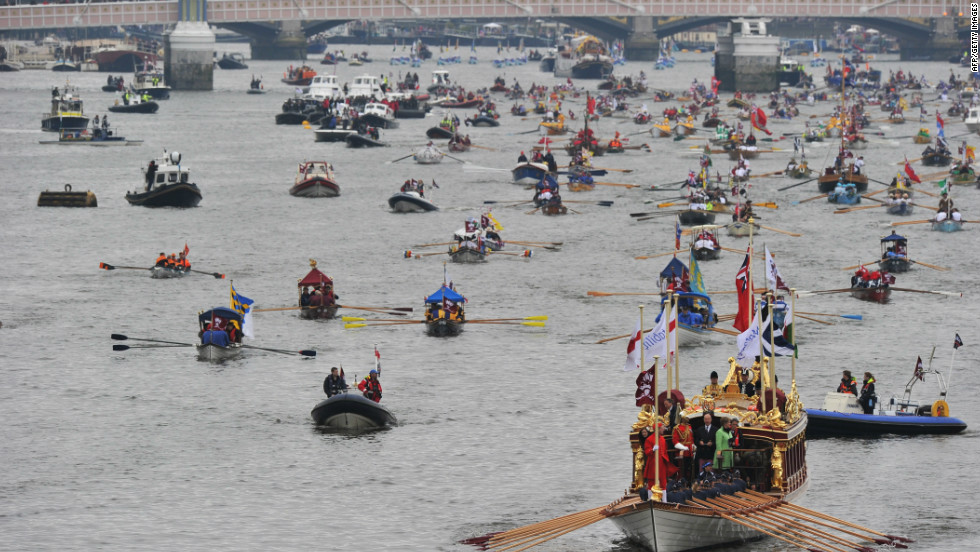 The queen's royal barge, Gloriana leads the way as the River Thames is awash with color from flotilla participants.