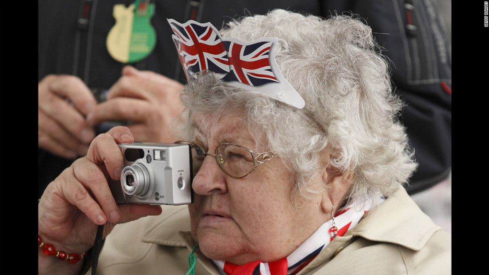 A woman takes pictures of the festivities Sunday near Tower Bridge during the Thames royal pageant.