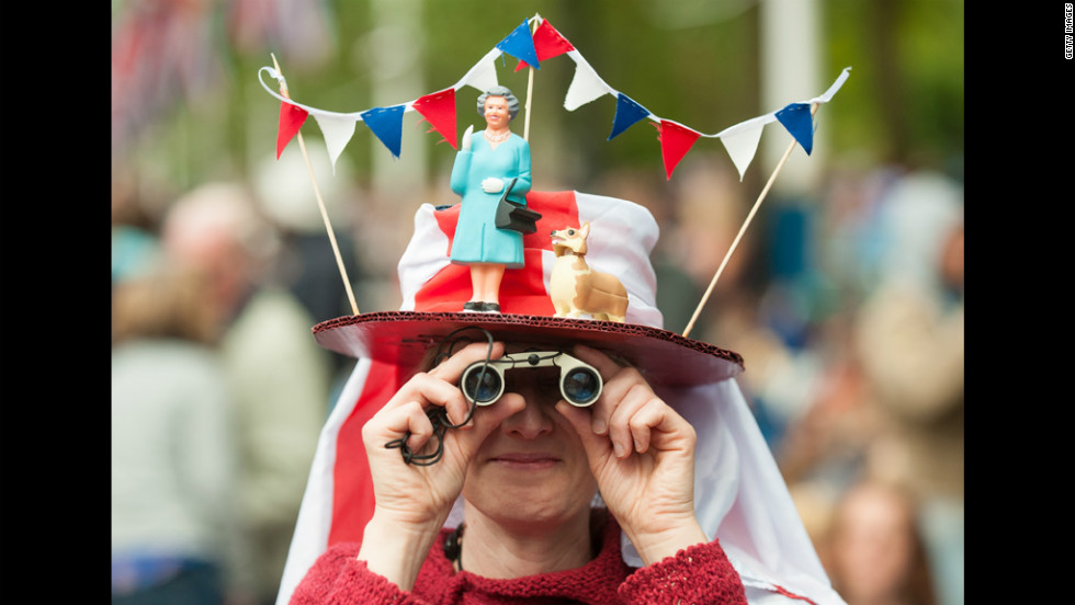 A woman with an elaborate hat featuring a miniature Queen Elizabeth II and her corgi awaits the start of the Diamond Jubilee concert Monday in London.