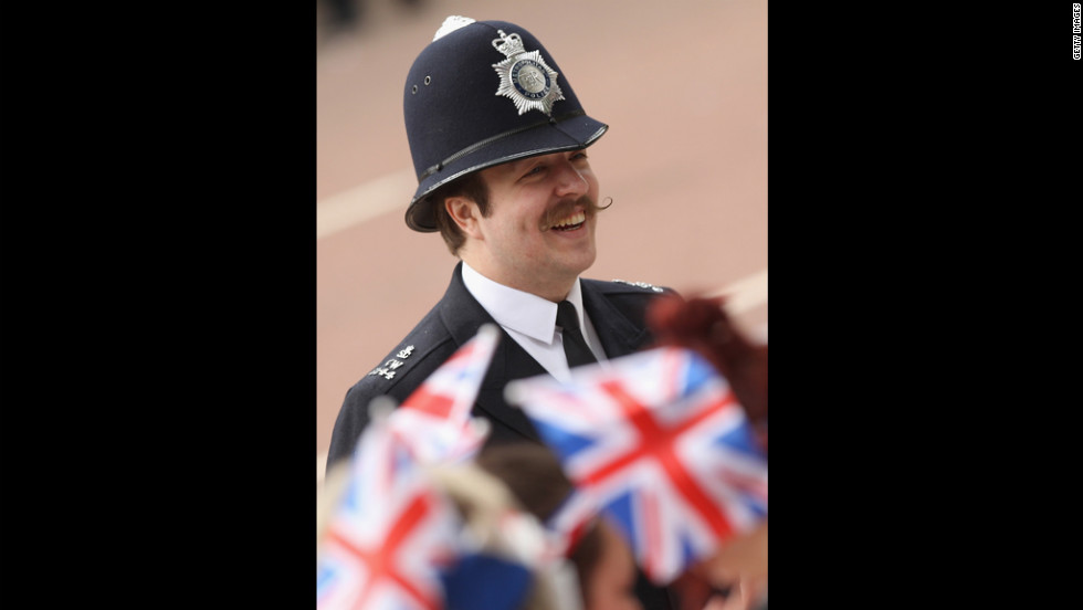 A police officer converses with the crowd along the royal procession route Tuesday in London.