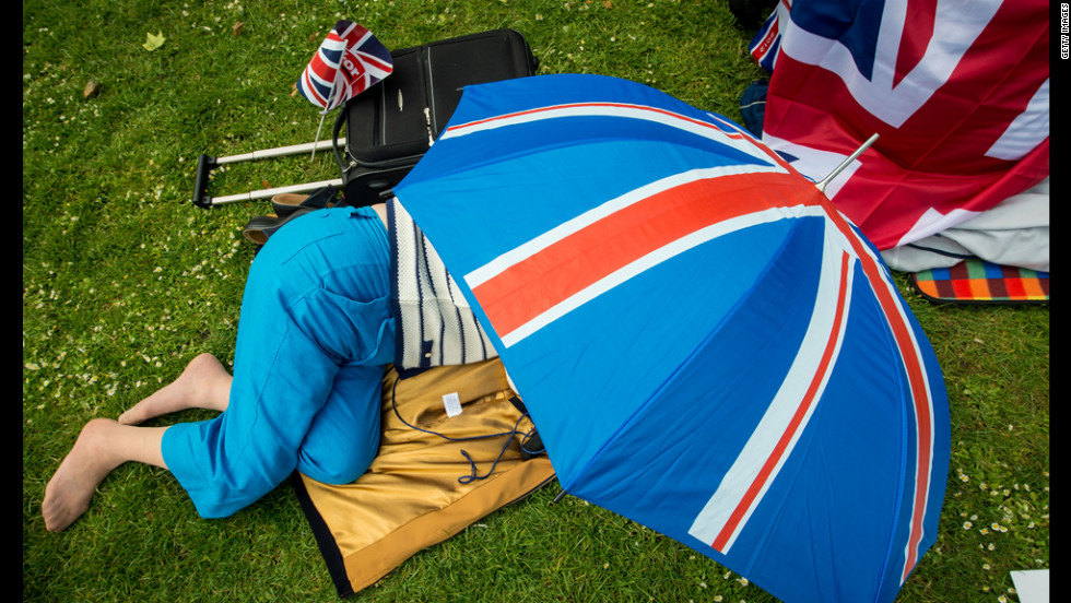 A woman takes refuge under a Union Jack umbrella in St Jame's Park.