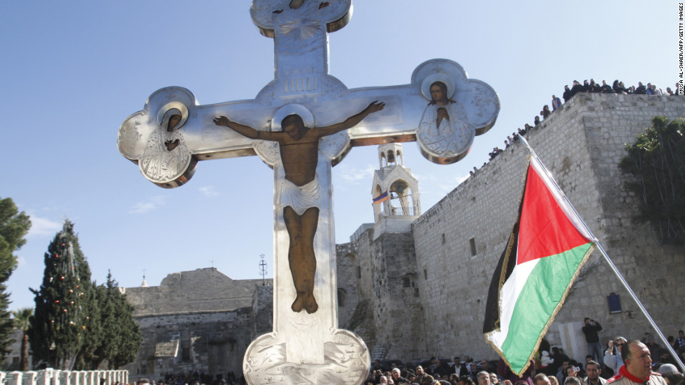 A cross held aloft in Manger Square, next to a Palestinian flag. One of Christianity's holiest sites, the Church of the Nativity is one of the biggest tourist destinations in the Palestinian territories, and drew about two million visitors last year.